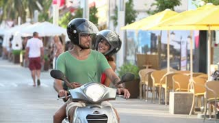 Slow Motion Shot Of Couple Riding Motor Scooter On Road