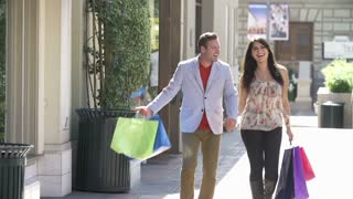 Slow Motion Shot Of Couple Shopping In Mall With Bags