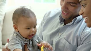 Slow Motion Shot Of Family Playing With Baby Son At Home