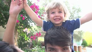 Slow Motion Shot Of Family Relaxing In Garden Together