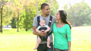 Slow Motion Shot Of Family With Baby Carrier Walking In Park