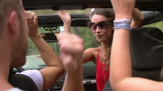 Slow Motion Shot Of Friends Dancing In Back Of Open Top Car