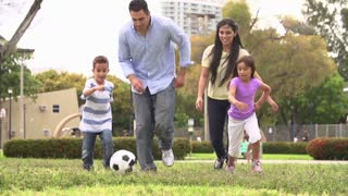 Slow Motion Shot Of Hispanic Family Playing Soccer Together