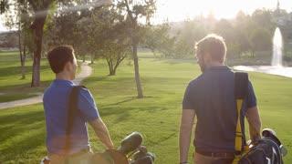 Slow Motion Shot Of Male Golfers Walking Along Fairway