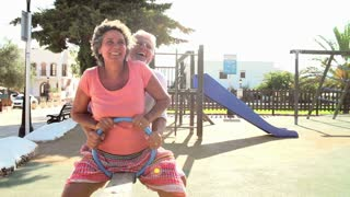 Slow Motion Shot Of Mature Couple On Seesaw In Playground