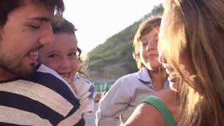 Slow Motion Shot Of Parents Giving Children Piggyback Ride