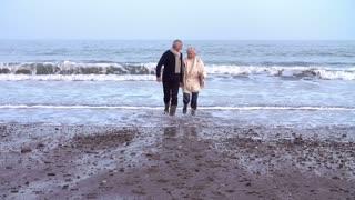 Slow Motion Shot Of Senior Couple Running Along Winter Beach