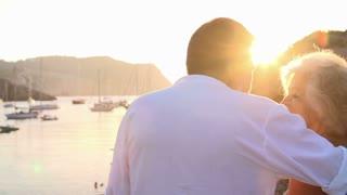 Slow Motion Shot Of Senior Couple Watching Sunset Over Port