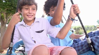 Slow Motion Shot Of Two Boys On Swing In Playground