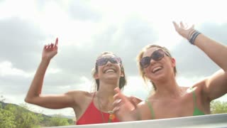 Slow Motion Shot Of Women Dancing In Back Of Open Top Car