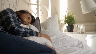 Slow Motion Shot Of Young Woman Lying On Bed Hugging Pillow