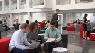Student group studying together in a busy modern university lobby, shot on R3D