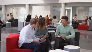 Student group studying together in a modern university lobby, shot on R3D