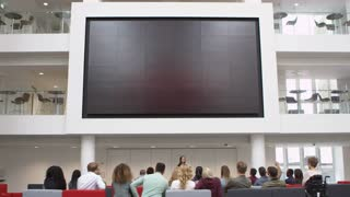 Students at a lecture watch a big screen in a university atrium, shot on R3D