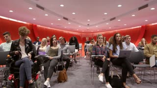 Students sit facing camera in a modern university classroom, shot on R3D