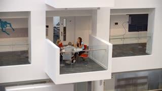 Students socialise on a mezzanine in a university building