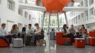 Students socialising in the lobby of a university, low angle