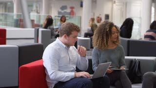 Students studying together in a modern university lobby, pan, shot on R3D