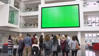 Students under big AV screen in university atrium, back view, shot on R3D