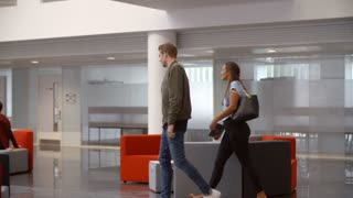 Students walking through meeting area in a university lobby