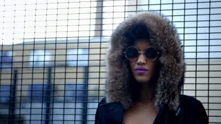 Stylish Fashion Blogger Stands By Fence In Urban Street