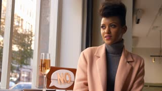 Stylish Woman Sitting In Window Of Bar Enjoying Drink