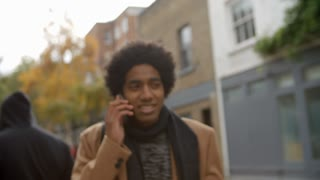 Stylish Young Man Making Phone Call On City Street