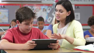 Teacher And Pupil Using Digital Tablet In Class
