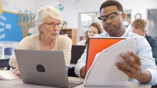 Teacher and student using laptop at an adult education class