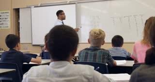 Teacher asks question in math class, back view, shot on R3D