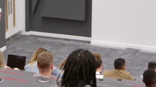 Teacher at lectern in lecture theatre, back row student POV, shot on R3D