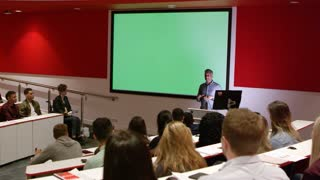 Teacher at lectern in lecture theatre presenting to students, shot on R3D