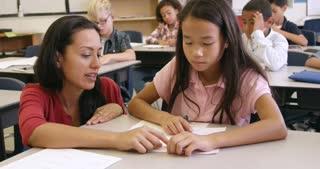 Teacher helping Asian schoolgirl at her desk, shot on R3D