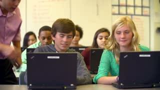 Teacher Helping High School Students Using Laptops In Class