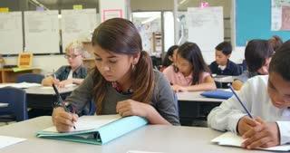 Teacher helping Hispanic schoolgirl at her desk, shot on R3D