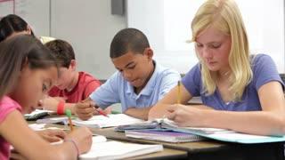 Teacher Helping Pupils In Class