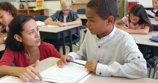 Teacher helps schoolboy in class, close up, shot on R3D