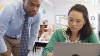 Teacher helps woman using laptop at an adult education class