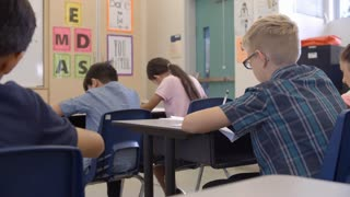 Teacher kneeling to help a 5th grade schoolboy at his desk