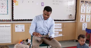 Teacher reading kids a story in school, handheld view