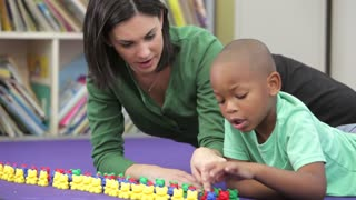 Teacher Showing Boy How To Count With Plastic Toys