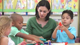 Teacher Sits With Group Of Children Using Construction Kit