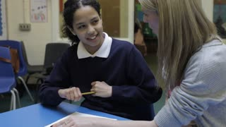 Teacher Working With Female Pupil At Desk