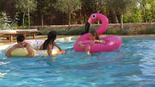Teenage friends have fun with inflatables in a swimming pool, shot on R3D