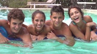 Teenage Friends Having Fun On Airbed In Swimming Pool