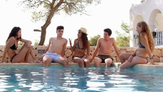 Teenage friends sitting at the edge of a swimming pool talking, shot on R3D