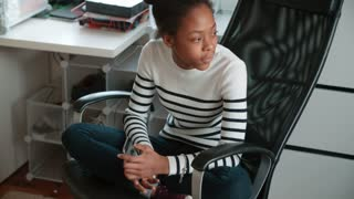 Teenage Girl Sitting In Chair And Talking To Friends