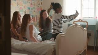 Teenage Girls In Bedroom Taking Selfie Using Mobile Phone