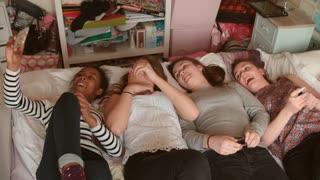 Teenage Girls Lying On Bed Taking Selfie Using Mobile Phone