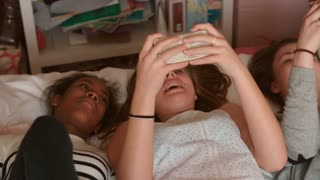 Teenage Girls Lying On Bed Using Mobile Phones At Home